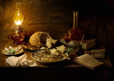 A rest from writing with a plate of sardines, spring onions and a glass of red wine in the warm glow of the oil lamp.